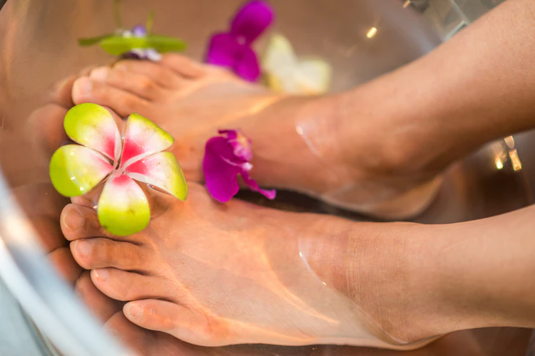 A person soaking their feet in a tub of water with floating flowers