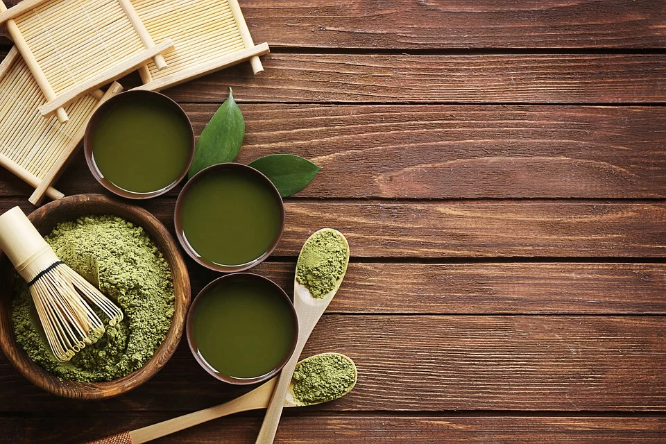 Green matcha powder and drinks inside bowls, cups, and spoons, on a wooden surface