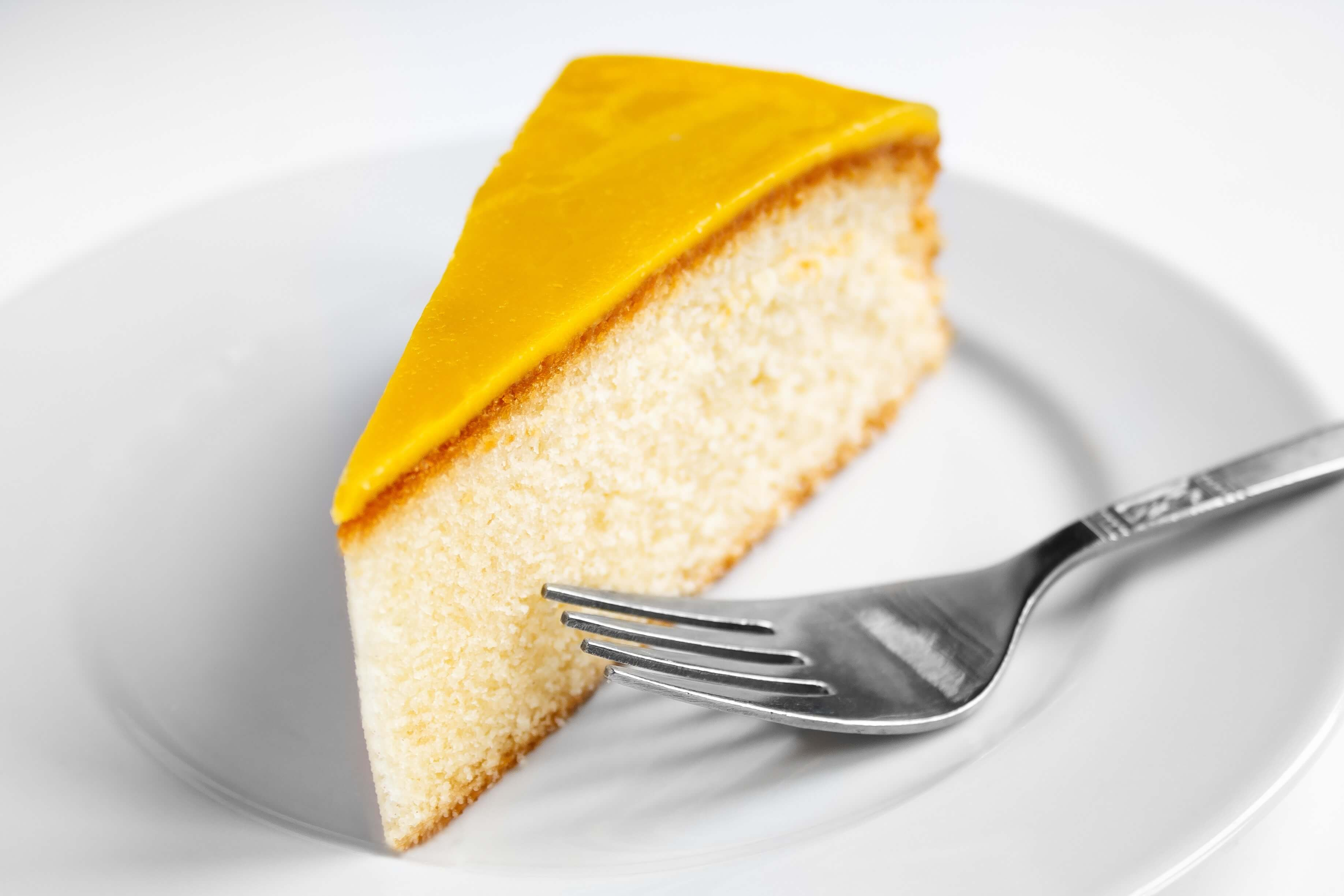 A slice of cake on a white plate with a fork