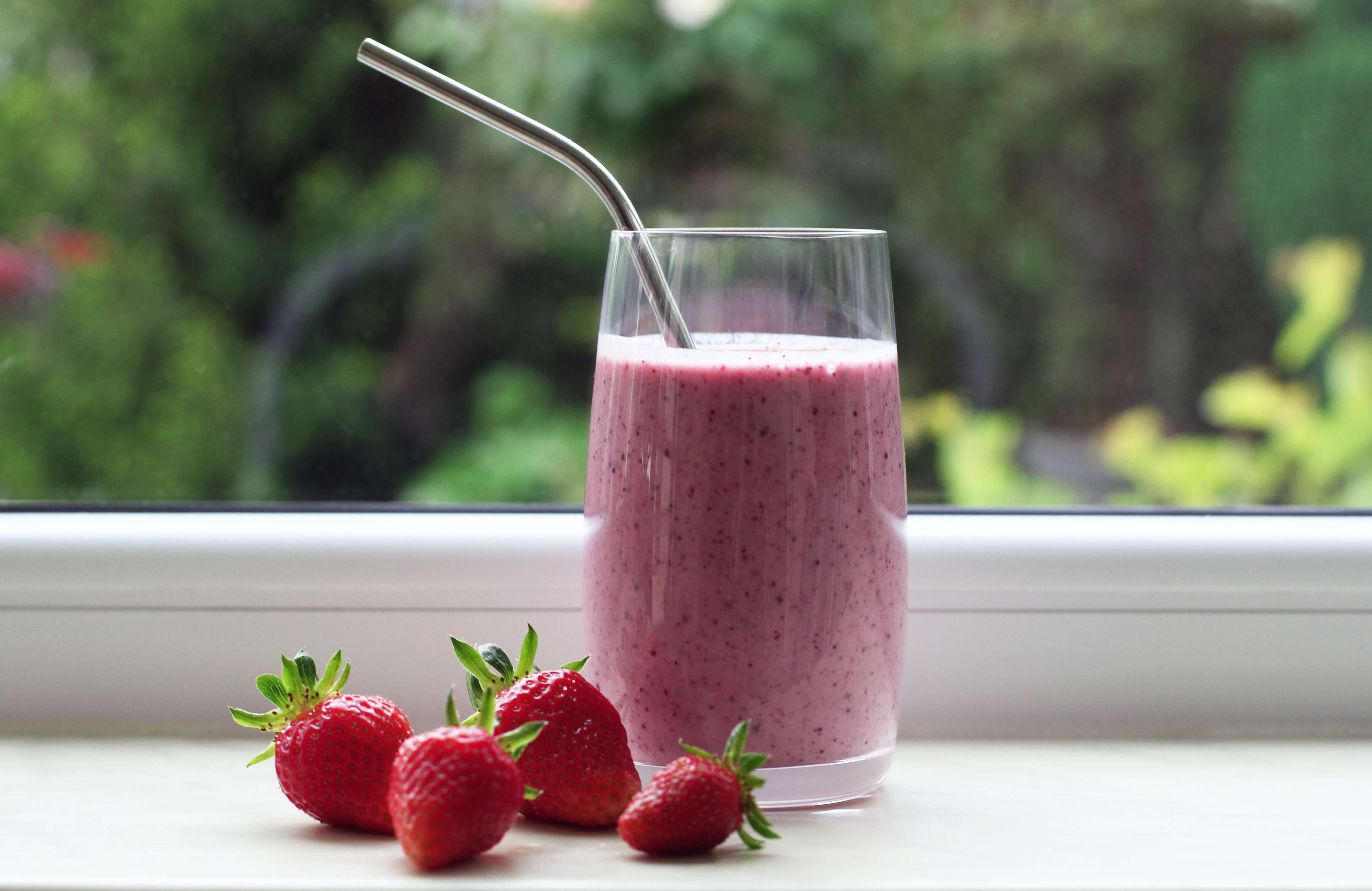 Strawberry milkshake in a clear glass placed in front of a window