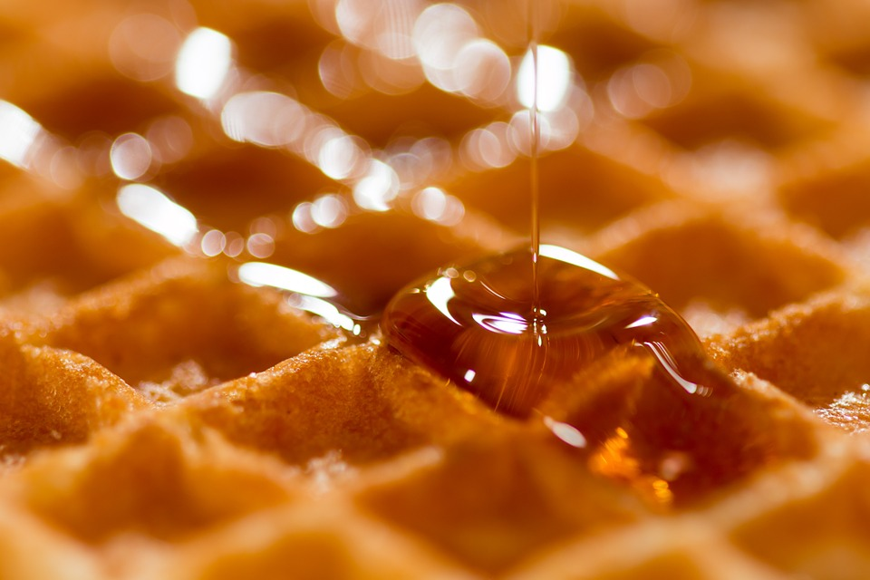 Drizzling golden brown syrup on a waffle