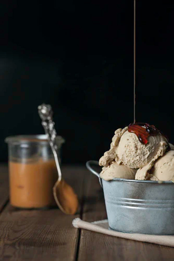 A dish of almond butter ice cream with a container of almond butter beside it