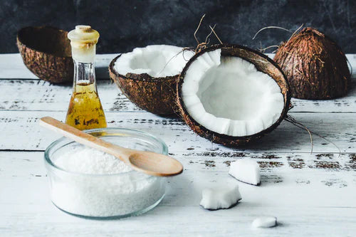 Fresh coconuts, oil, and white powder on a table