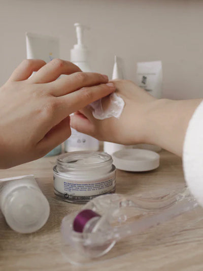 A person rubs lotion on their hand with beauty products in the background