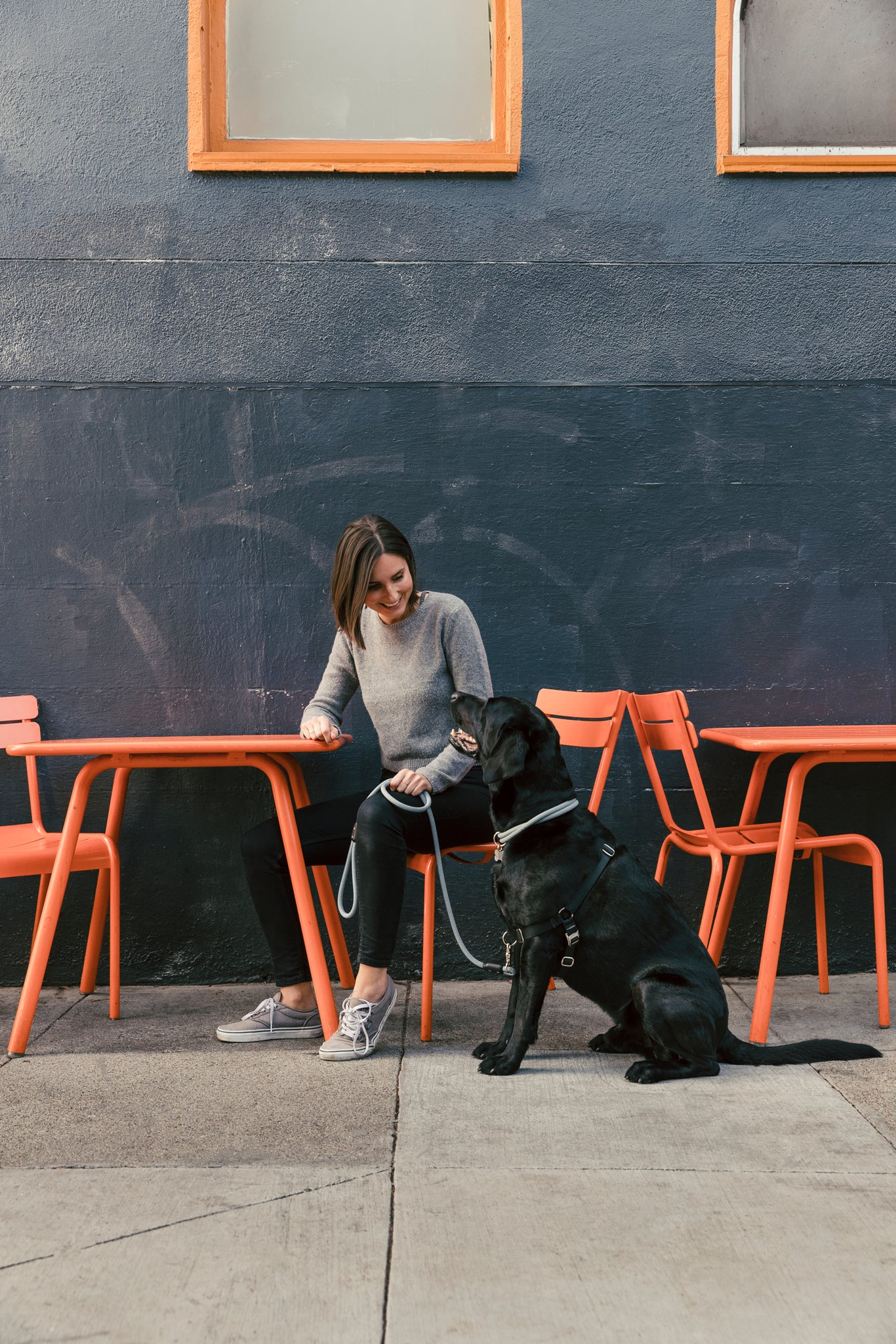 Woman sits outside on city street with dog - Atlas Pet Company Top Five Towns for Dog Lovers