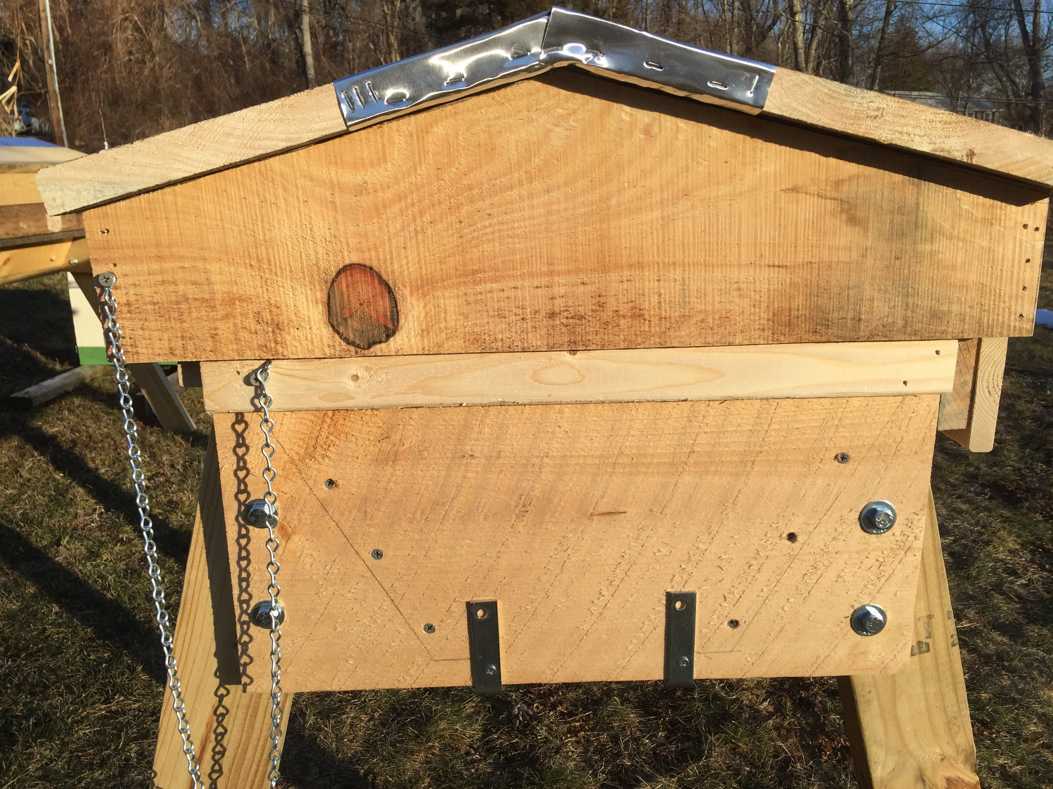 Legs are bolted outside of the hive so you can remove them in the event that you need to move the hive. The bottom board is attached with an L-bracket. It can be hung with a gap below the hive to perform mite counts.
