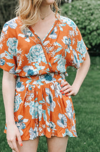 rust romper with blue floral print ladder trim flowy sleeves