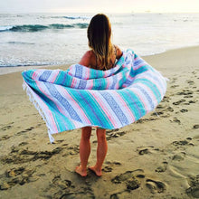 open blanket on beach pink blue green