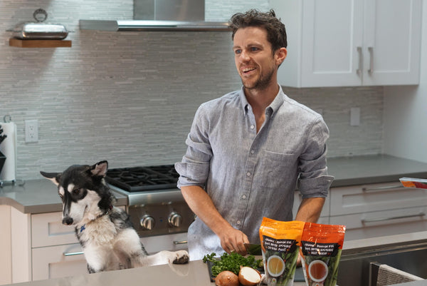 Connor from Bluebird Provisions organic bone broth chopping vegetables with his dog