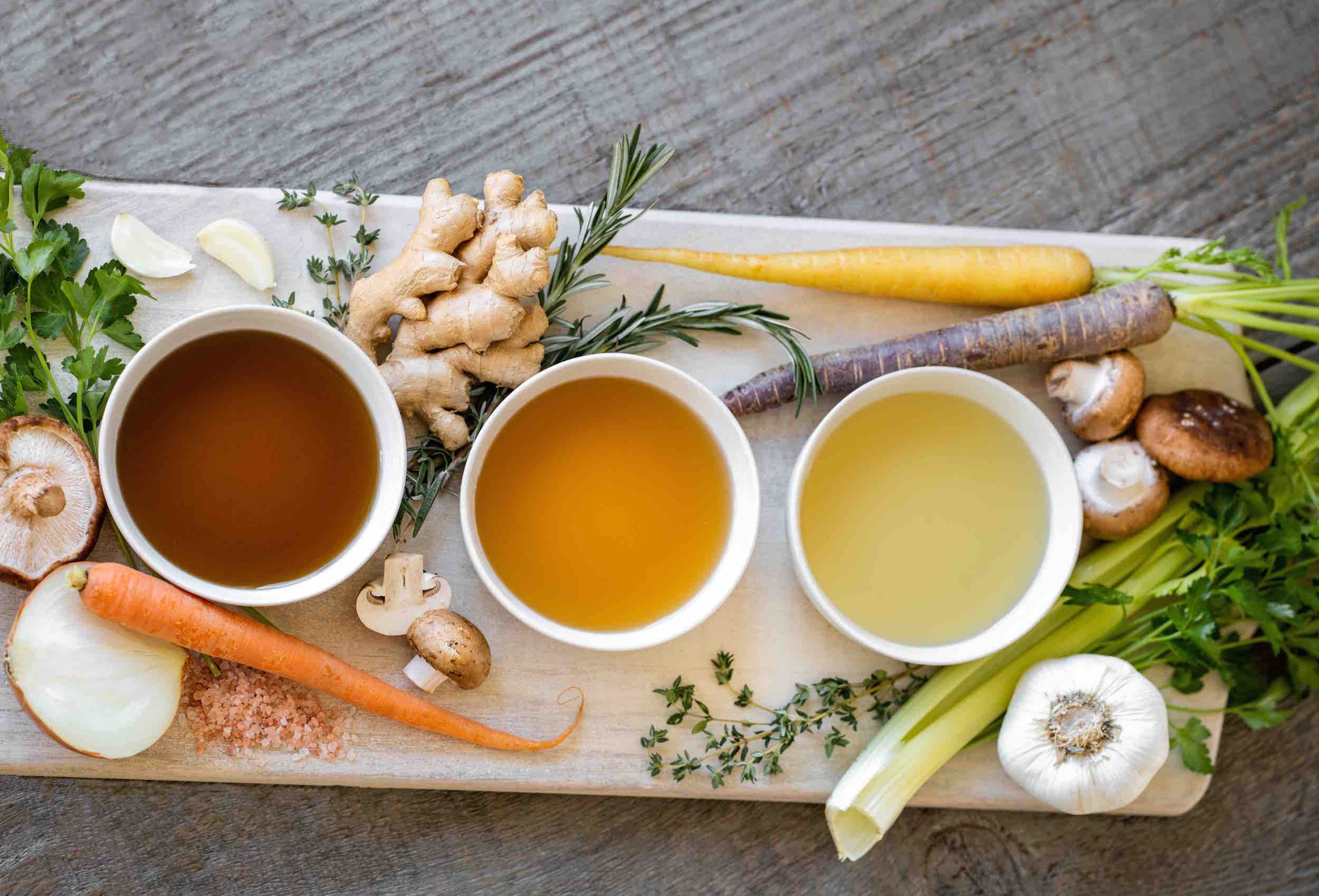 Organic bone broth in bowls with ingredients