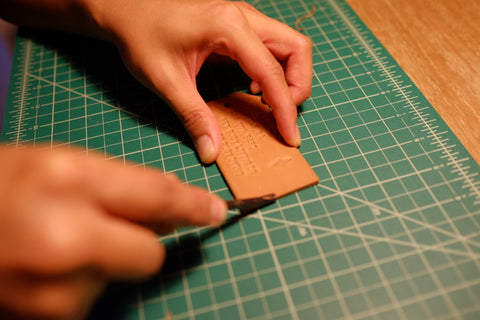 beveling the leather luggage tag edges