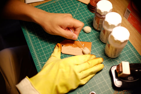 applying olive oil to leather luggage tag face