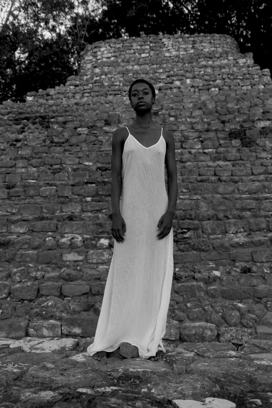 This is a black and white photo of a womand in a white slip dress syanding in front of a monument made of stones.