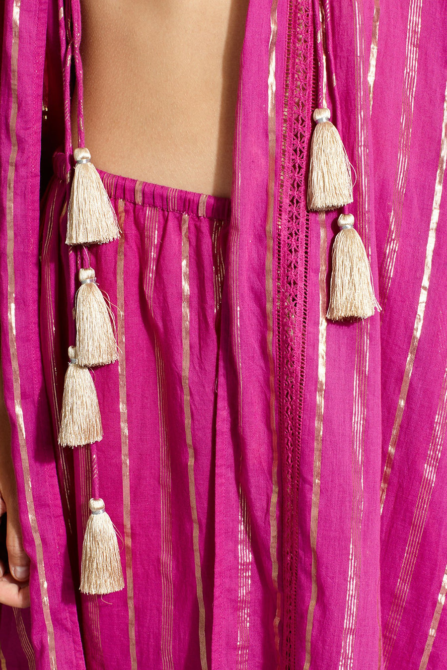 This is a detail photo of gold tassels that hang from magenta/pink colored pants and coat with gold metallic stripes.