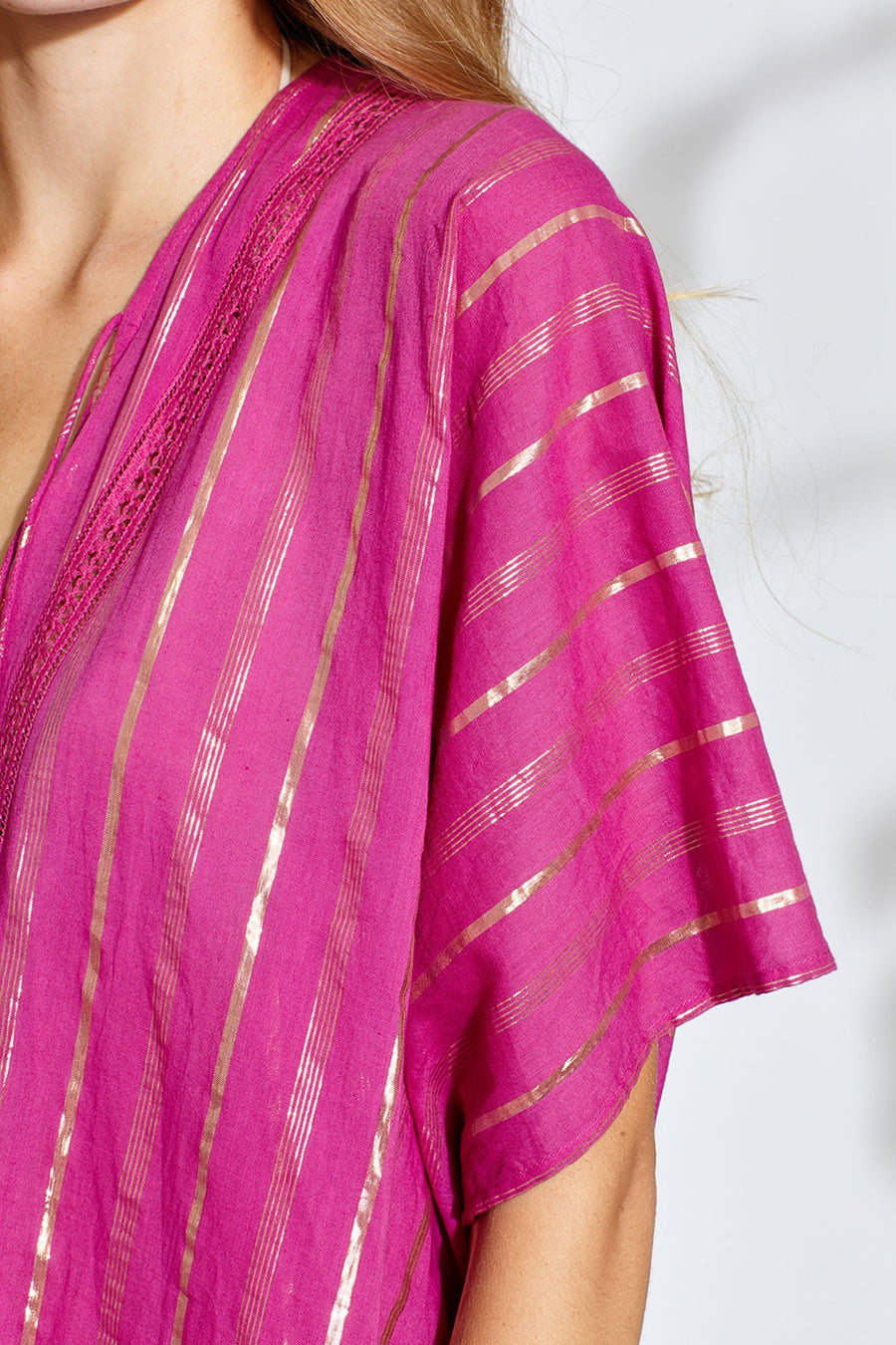 This is a detail photo of the shoulder of a magenta/pink colored coat with gold metallic stripes.