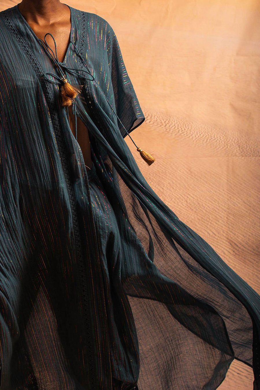 This is a detail photo of a blue cotton gauze coat with metallic stripe detailing. It is worn closed here with ties in the same fabric and gold tassels on the end.