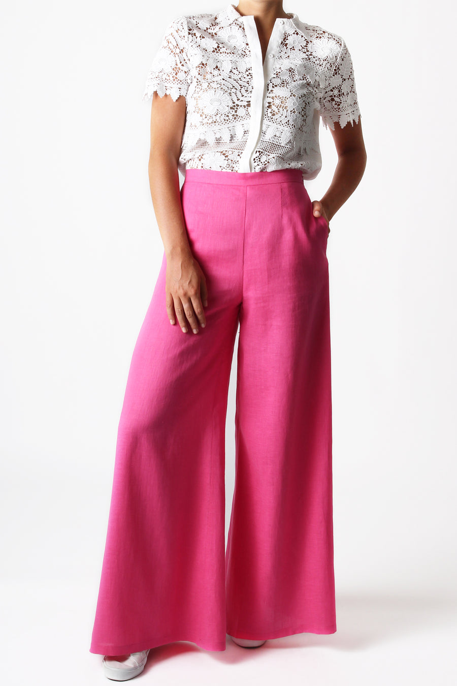 This is a photo of a woman from the neck down, she is wearing a button front, lace tired blouse tucked into a pair of bright pink, flare leg pants. She has her hand in the left side pocket of the pants.