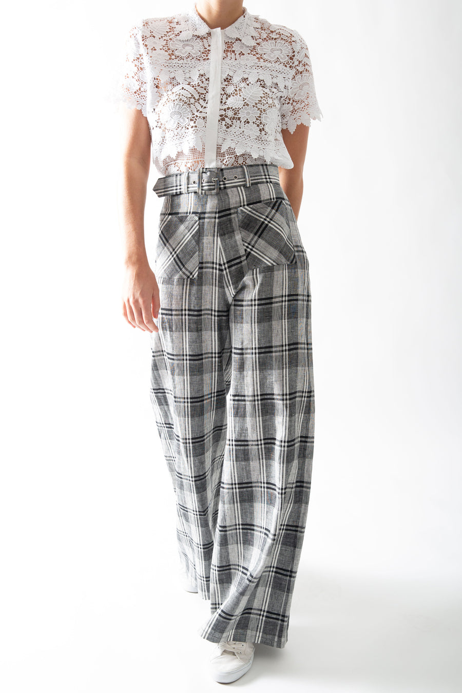 This is a photo of a woman from the neck down, she is wearing a lace, collared, button front top tucked into plaid wide leg pants. The top is a detailed floral lace embroidery, with leaf shaped scallops throughout.