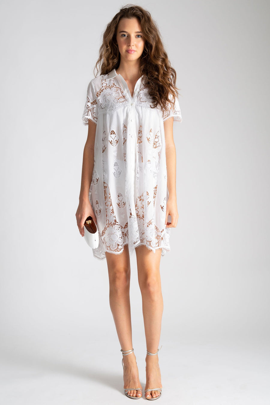 This is a photo of a woman wearing a white cotton babydoll coverup dress with lace embroidery in hibiscus inspired flowers. The dress buttons up the front and is not lined. Here, she styles it with heels and clutch.