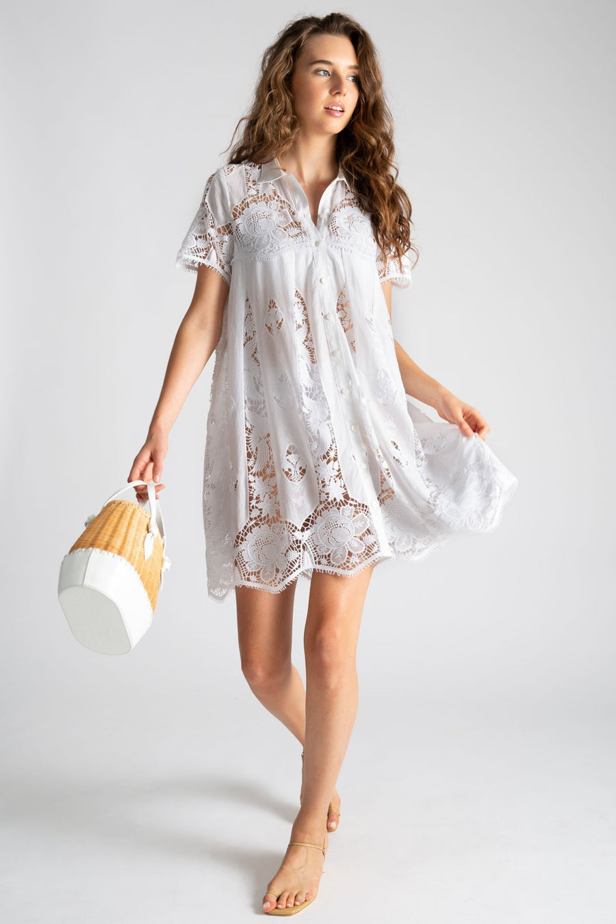 This is a photo of a woman wearing a white cotton babydoll coverup dress with lace embroidery in hibiscus inspired flowers. The dress buttons up the front and is not lined.