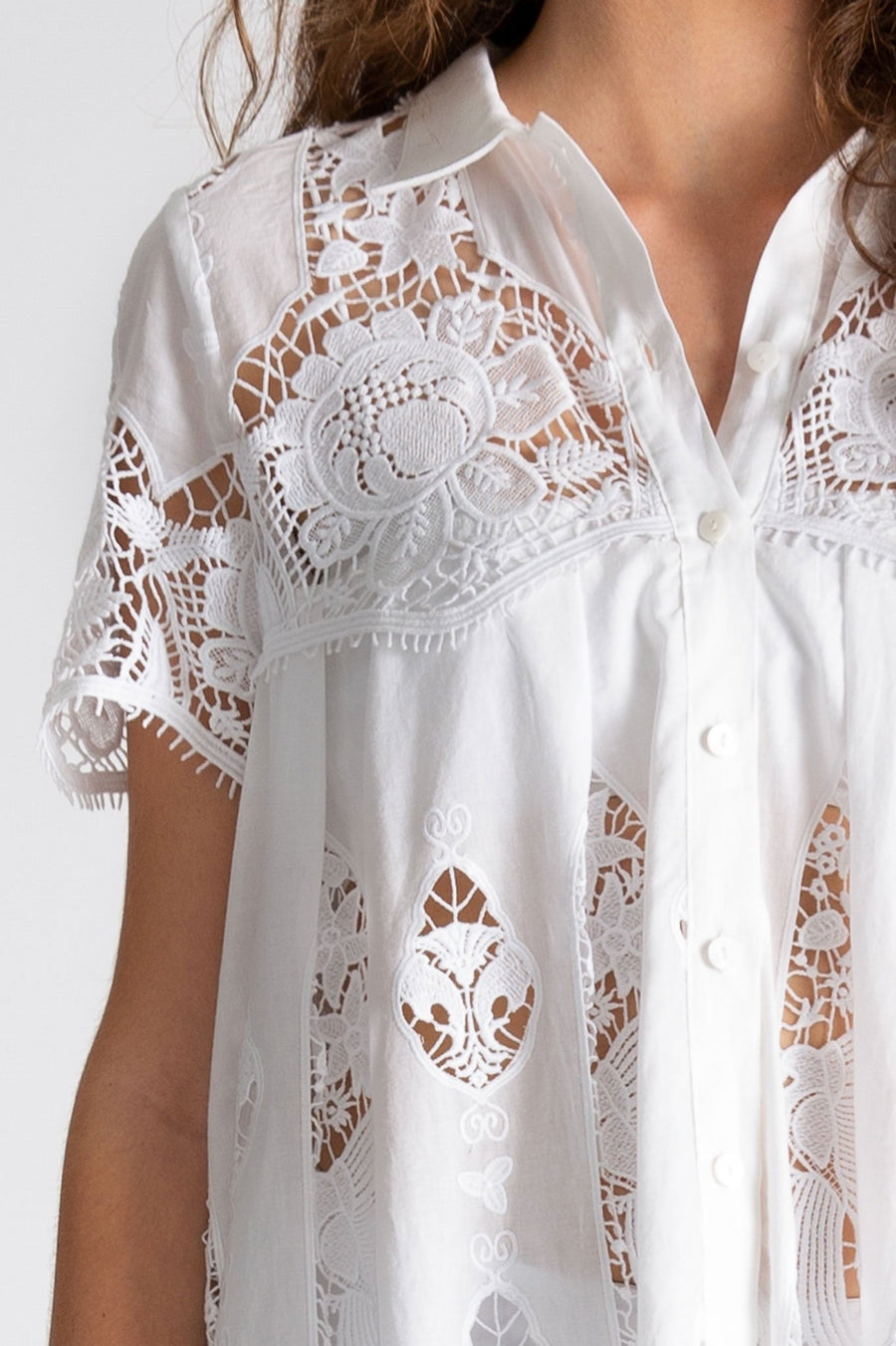 This is a detail photo of the white lace embroidery inspired by hibiscus flowers. The linen collar and button down front are visible here on the babydoll coverup dress.
