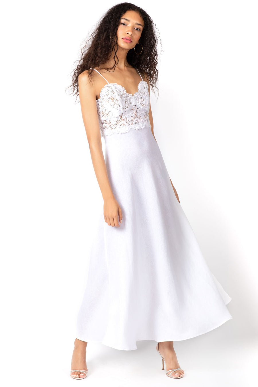 This is a photo of a woman wearing a floor length, pure white, linen and lace dress. The dress has spaghetti straps and a fully lace bodice, with a flowing linen skirt.