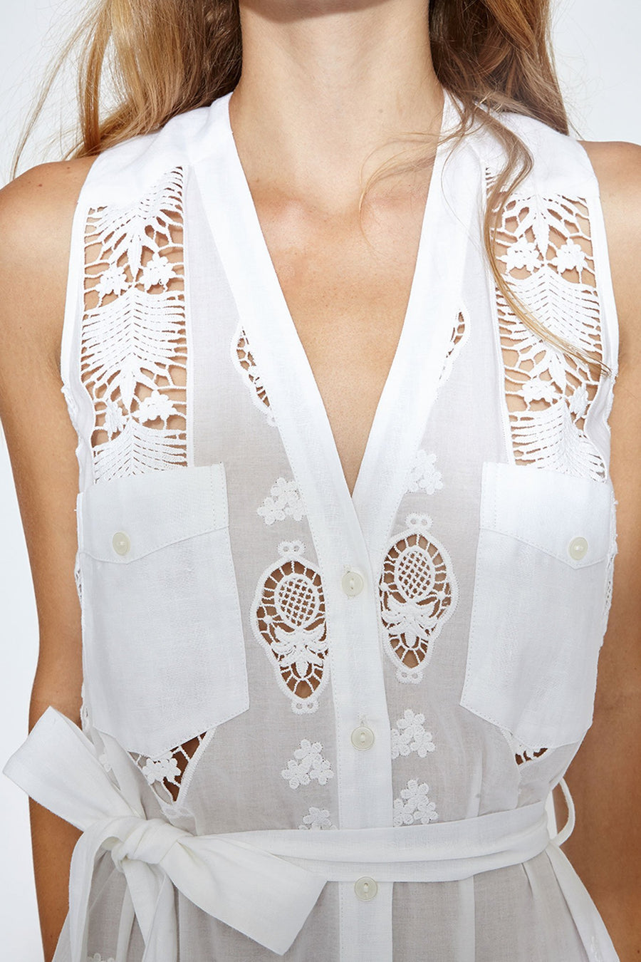 This is a detail photo of a v neckline on a white cotton embroidered dress. The photo shows details of the embroidery design with flowers and pineapples. The dress has two square solid white pockets on the chest.