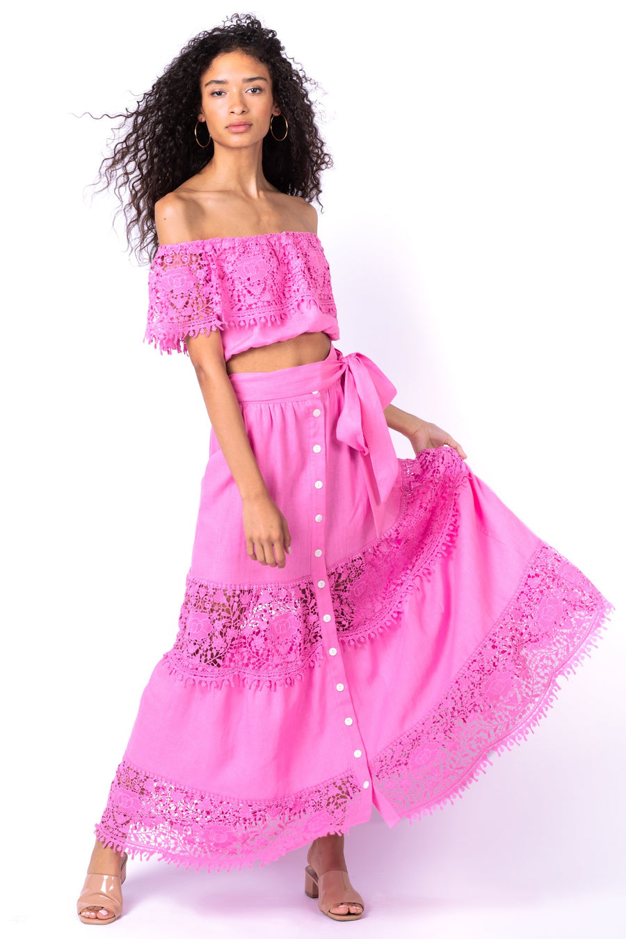 This is a photo of a woman wearing a pink, off the shoulder, linen top with a matching pink lace trim around the shoulders. It is paired with a matching pink, button front, linen and lace tiered skirt.
