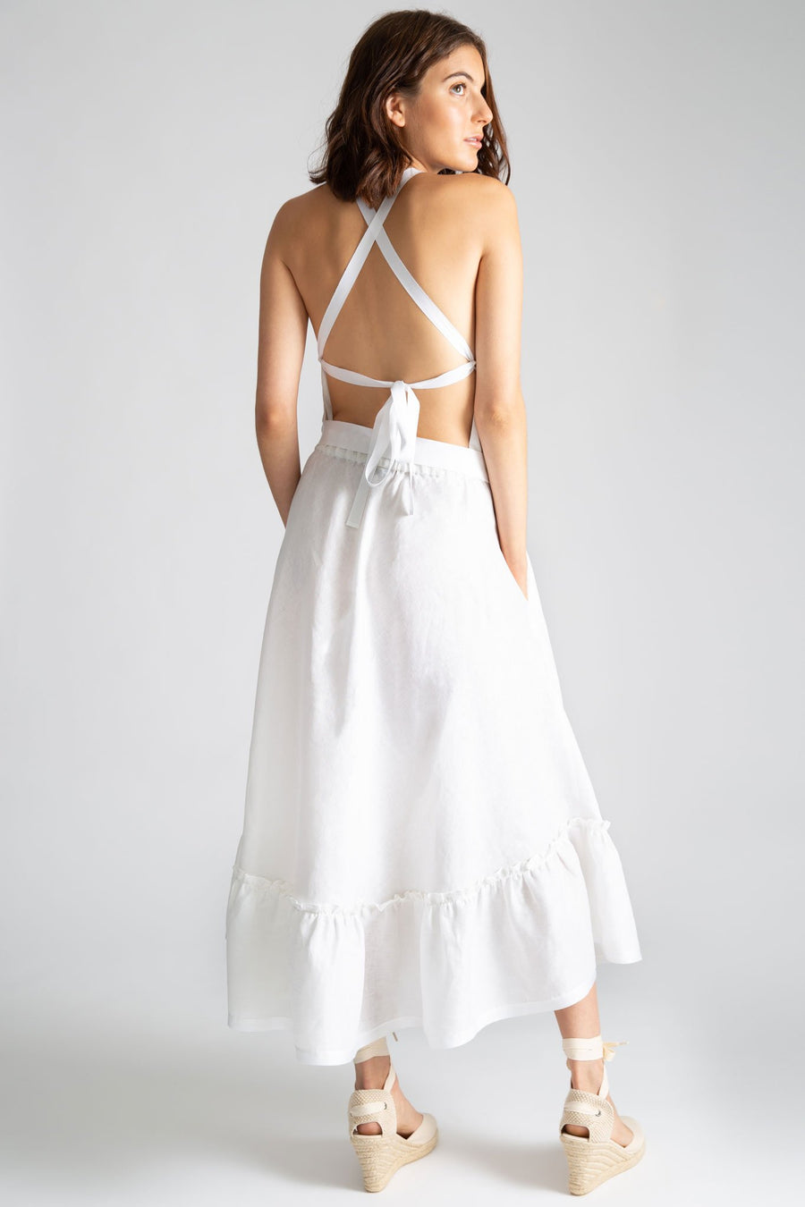 This is a photo of the back of a solid white linen dress. The back features an open criss-cross look with gross grain ribbon and side pockets on seam.