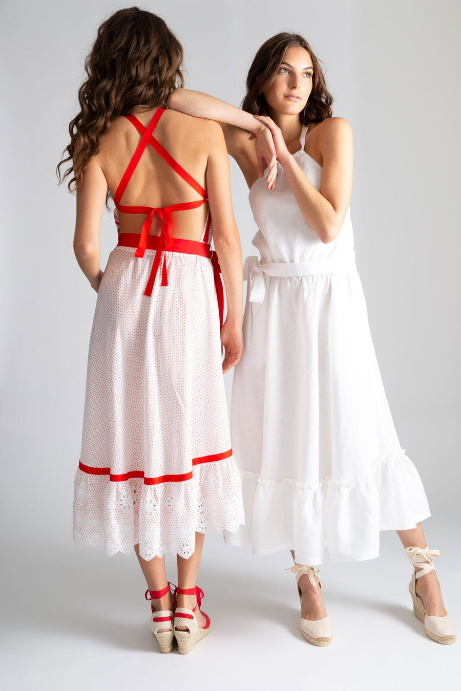 This is a photo of a woman wearing a white linen dress with halter neckline, waistline elastic and removable gross grain ribbon. It has a bottom ruffle detail that falls just above the ankle and is finished with a gross grain plain white ribbon. There is a second girl standing next to her, wearing the same dress in a red printed cotton with red gross grain ribbon and cotton embroidery details at the skirt hem.