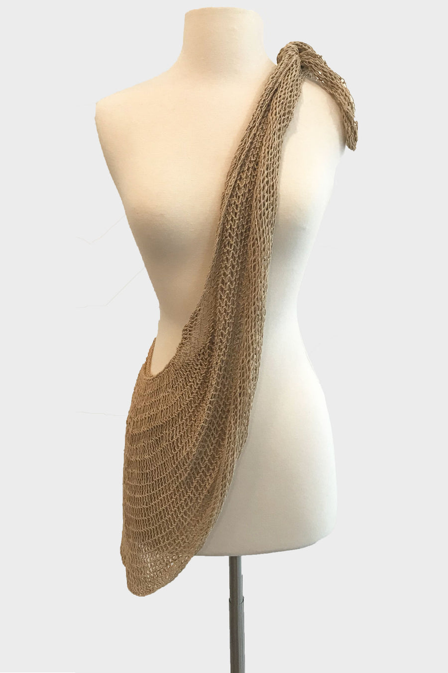 This is a photo of a natural-colored bag draped across the mannequin, tied on one shoulder and resting on the opposite hip.