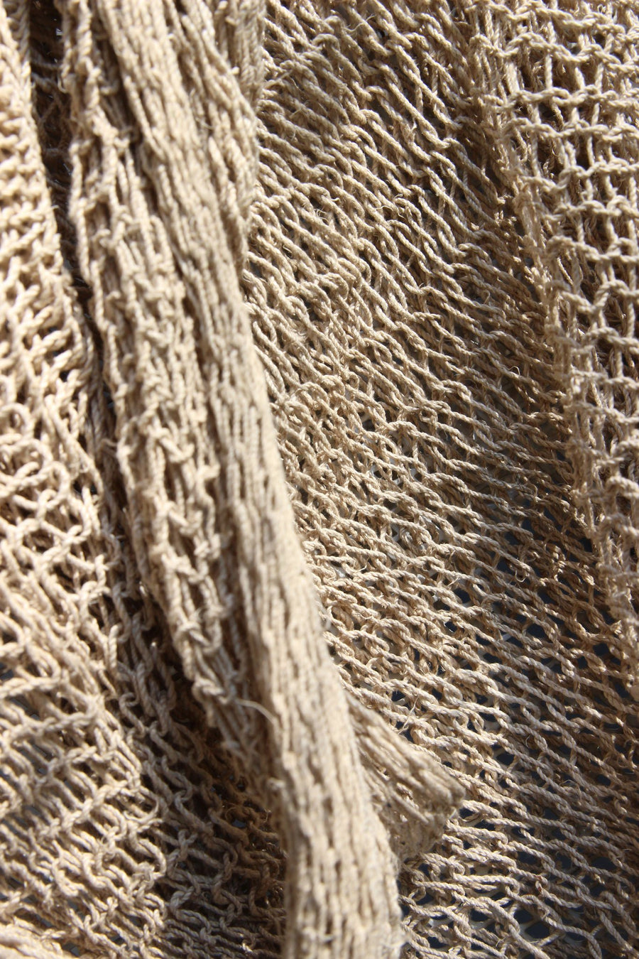 This is a detail photo of the texture of a natural-colored woven bag.