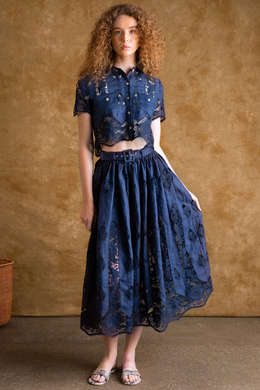 This is a photo of a woman wearing a 2 piece navy blue linen and lace set. The crop top has 2 front square pockets and buttons up the front for closure. The mid length skirt has a removable belt, side pockets, and a scalloped hemline at the bottom.