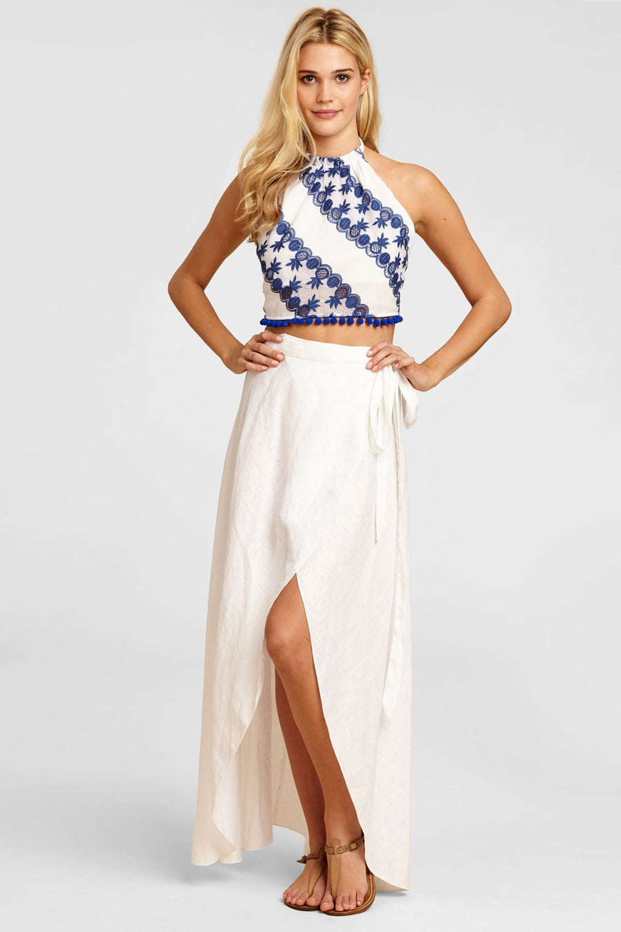 This is a photo of a white linen wrap skirt that splits open in the front and ties on one side. The skirt is worn here with a white and blue halter top with blue pineapples on it and blue pom poms at the hemline.