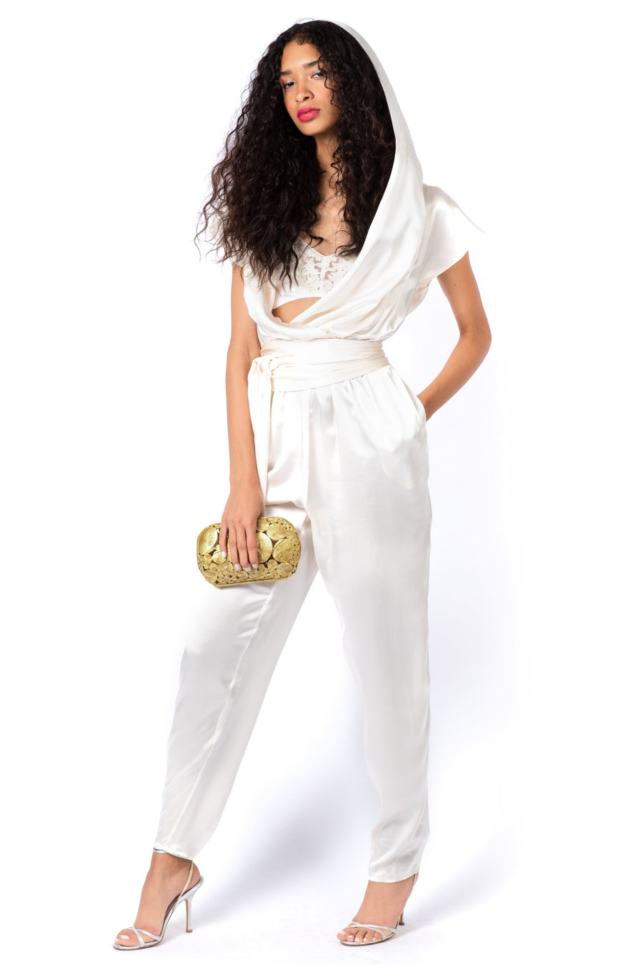 This is a photo of a woman wearing an ivory, silk charmeuse bralette that is trimmed with a delicate lace. With the bralette she is wearing an ivory, silk charmeuse, hooded jumpsuit.