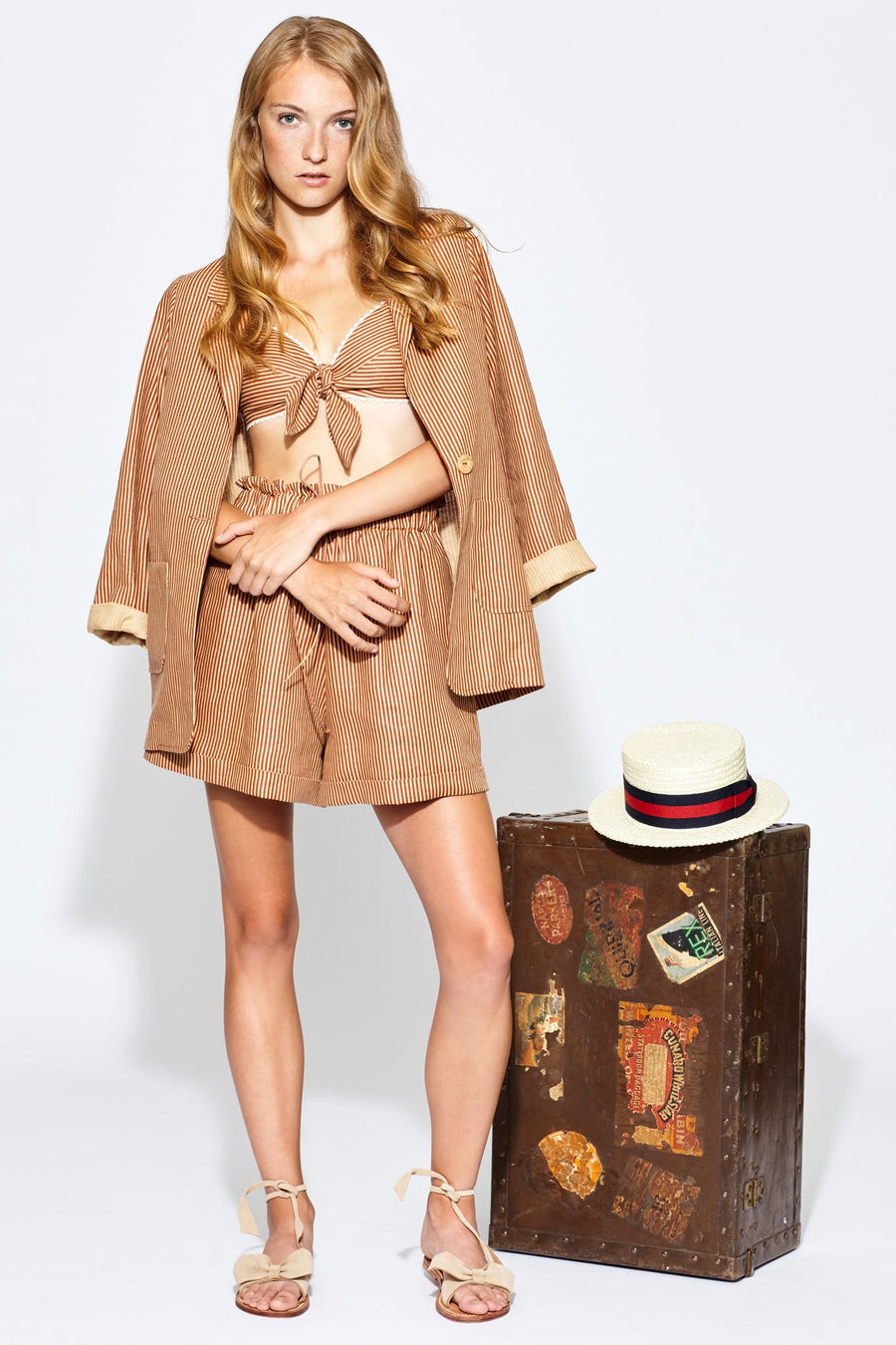 This is a photo of a woman a venetian striped three piece suit with a blazer, bralette, and shorts. She stands next to a rustic suitcase with a top hat on top of it.