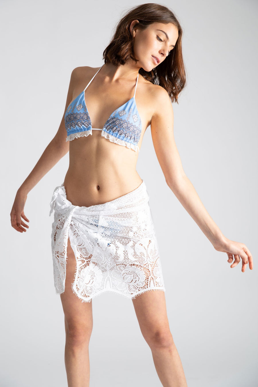 This is a photo of a woman wearing an all white lace mini pareo, tied on one side over a blue bikini. She glances over one shoulder.