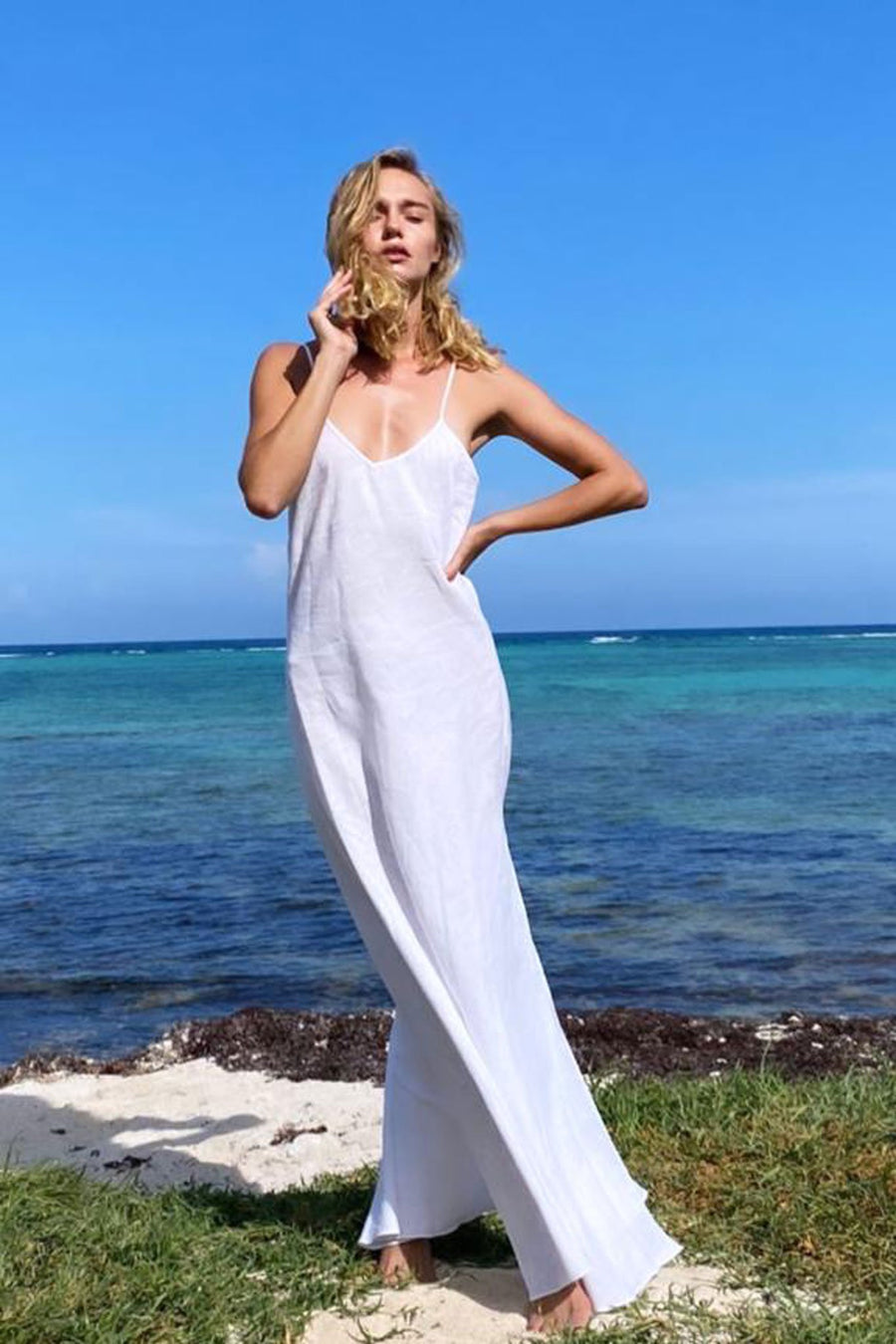 This is a photo of a woman wearing a white linen slip dress with v neck front and side leg slit. She is standing on a beach overlooking the ocean.