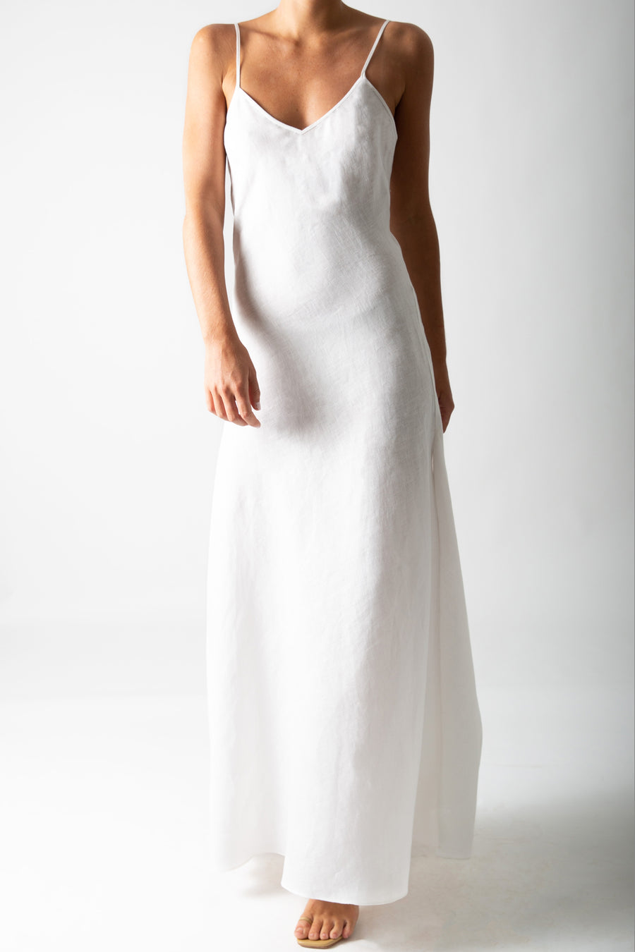 This is a photo of a woman from the neck down, she is wearing a white linen slip dress that reached to the floor.