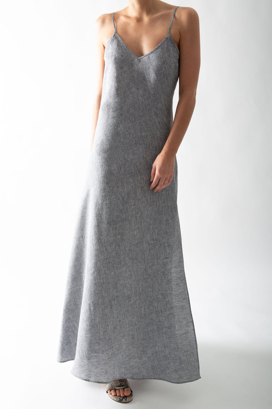This is a photo of a woman from the neck down, she is wearing a gray chambray slip dress.