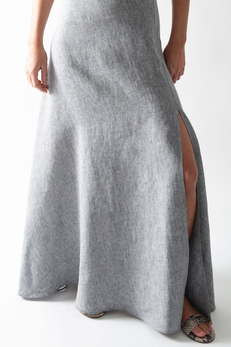 This is a close-up photo of the bottom of the slip dress, showing off the side slit that comes up above the model's knee.
