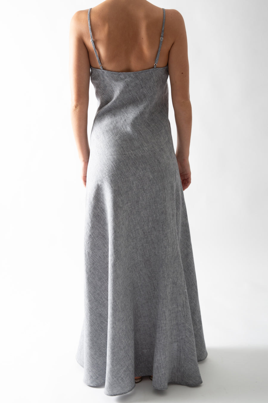 This is a photo of the back of a woman from the neck down. She is wearing the gray chambray slip dress. The photo highlights the adjustable slider straps on the dress.