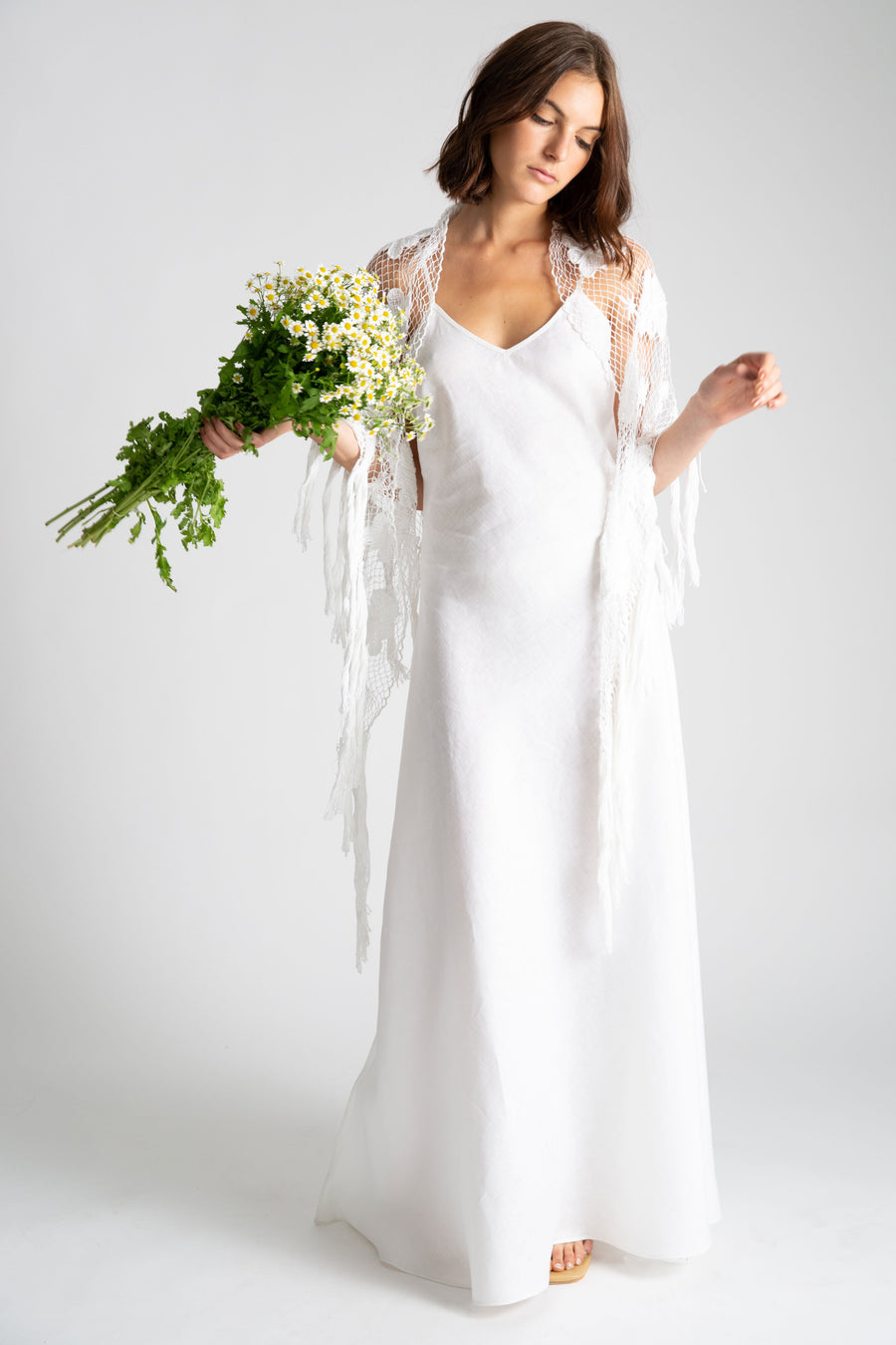 This is a photo of a woman wearing a white linen slip dress with v neck front and side leg slit. Over the slip dress, she wears a white hand knit shawl and holds a bouquet of daisy flowers.