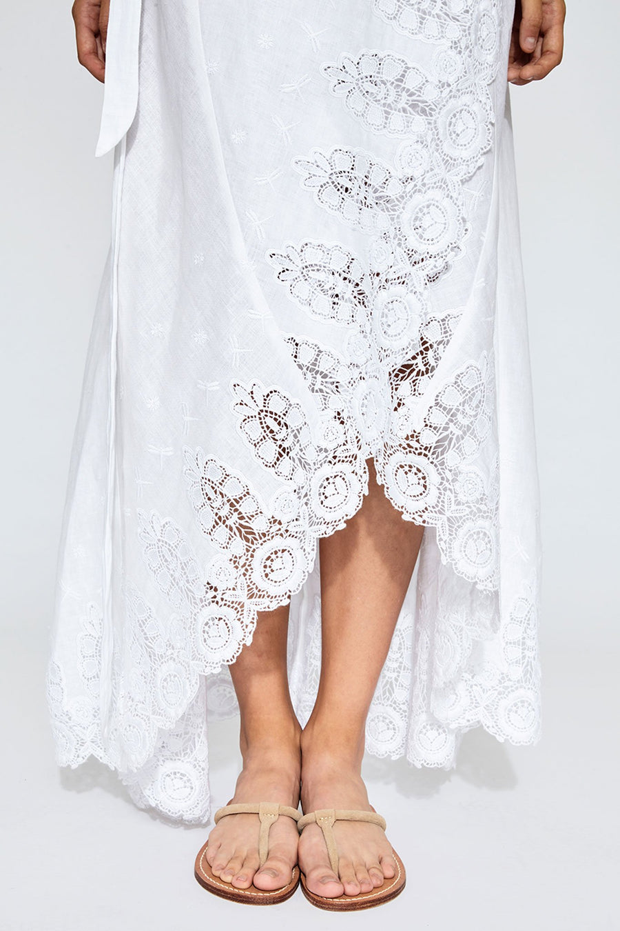 This is a detail photo of the front of a white linen and lace wrap skirt that splits in the front. The lace detailing shows flowers and dragonflies. She wears nude sandals.