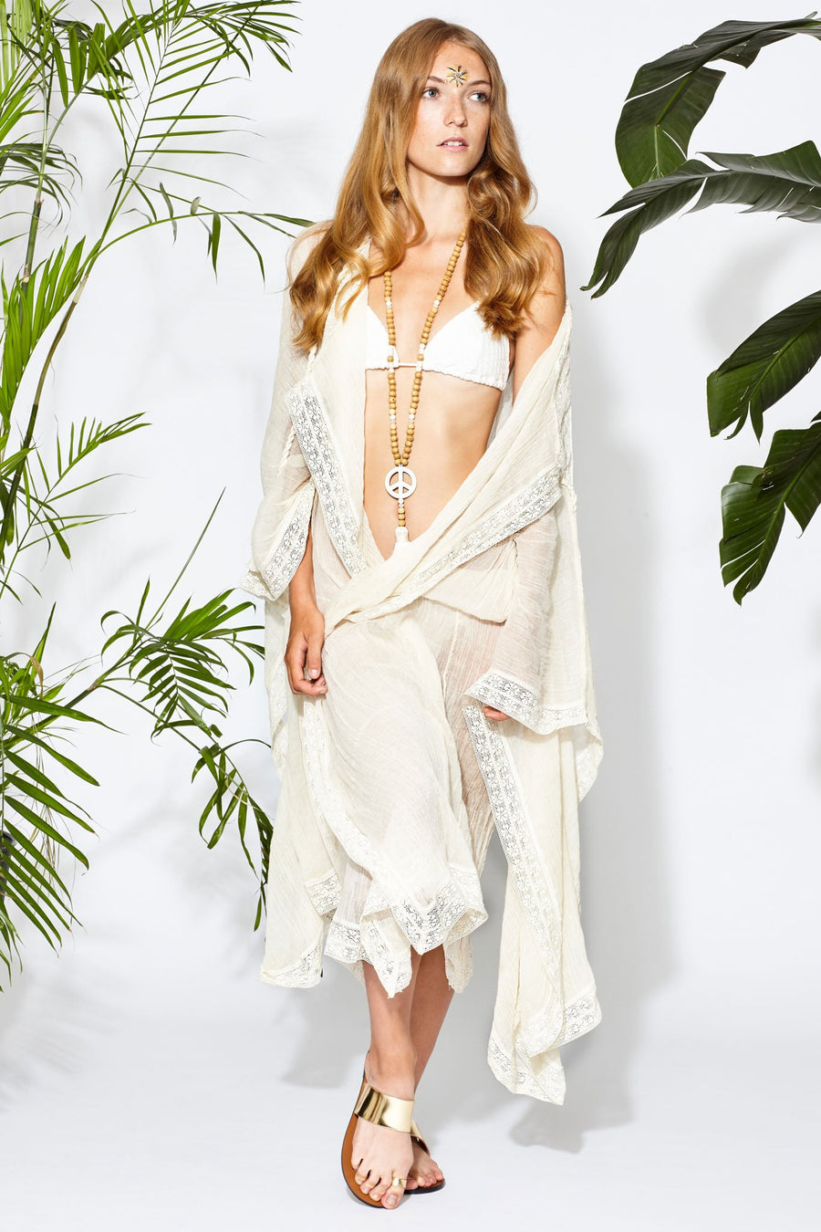 This is a photo of a woman wearing a natural colored cotton guaze coverup that is worn open and floor length. There is lace trim on the hems and rope tassels hanging from the top where the piece can be tied closed. She styles it here over a white bikini top with gold sandals and a wood beaded necklace with peace sign pendant.