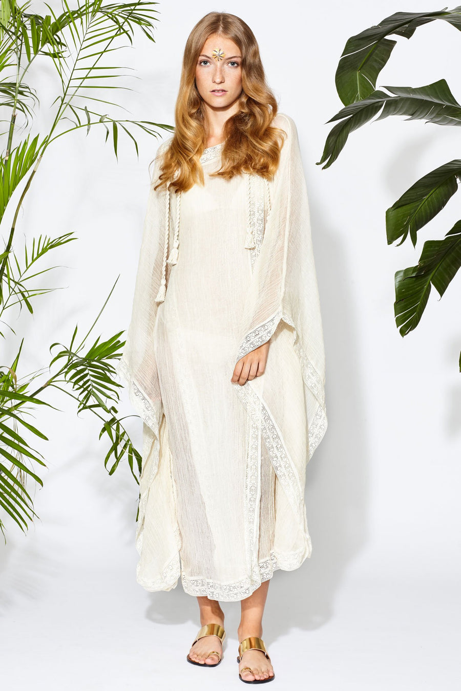 This is a photo of a woman wearing a natural colored cotton guaze coverup that is worn closed and floor length. There is lace trim on the hems and rope tassels hanging from the top where the piece was tied closed.