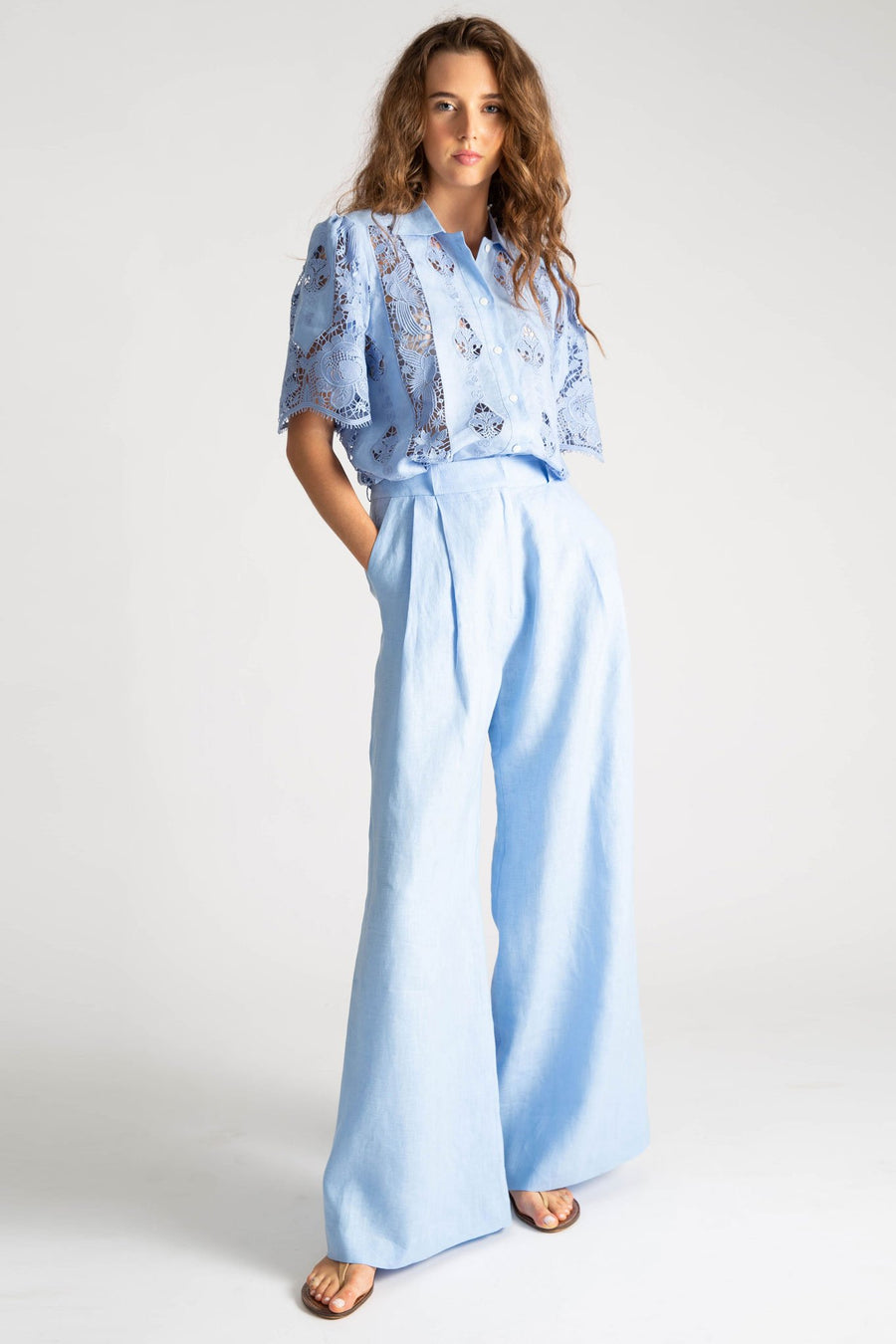 This is a photo of a woman wearing an all blue outfit. Her top is linen with lace embroidery with a button down front, linen collar, and short sleeves. The shirt is tucked into a pair of loose-fit solid blue linen pants with belt loops and side seam pockets. She styles the outfit with nude sandals.