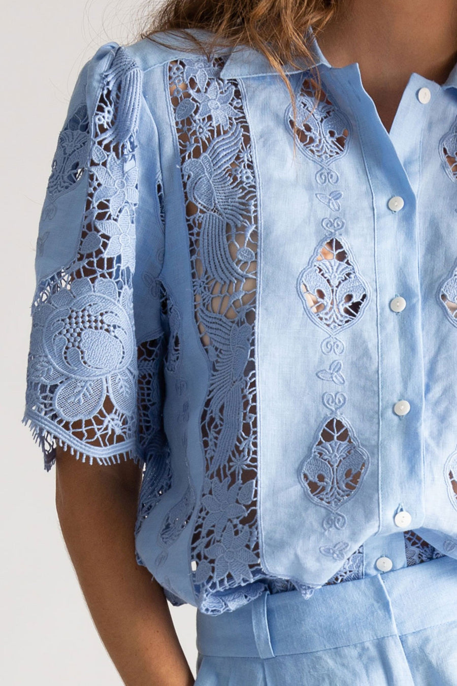 This is a detail photo of a woman wearing a blue linen and lace top with button down front and linen collar. The photo shows detail of the lace design which includes birds and flowers. The top has a short sleeve with gathering at the shoulder to add volume.