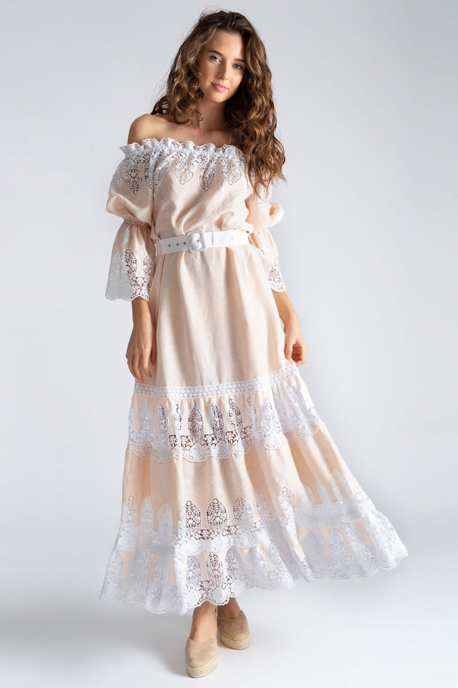 This is a photo of a woman wearing a floor length linen and lace dress that is off the shoulder with peasant sleeve. The neckline has white lace embroidery on the honey colored base linen and is styled with a solid white linen removable belt. There are 3 tiers of lace embroidery on the bottom of the dress.