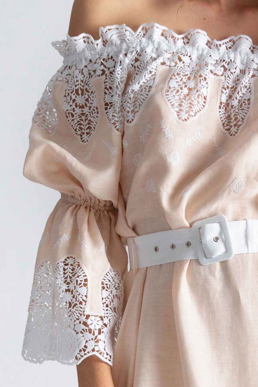 This is a detail photo of a peasant sleeve on a linen and lace gown. The sleeve has lace details, along with the neckline, that includes floral shapes.